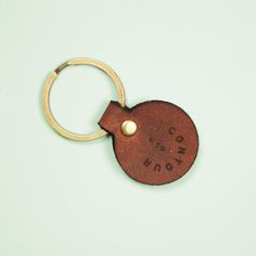 """Leather Key Fob - Off-Cut Fob - Fabricated from the off cuts, in order to minimize waste, this little key fob features the contour & co logo, attached to a 1 1/8"""" Antique brass key ring.  Handcrafted in Toronto, Canada.  Boomer Brown Leather  Size: 1"""" Diameter   #leather #wallet #keyring #keyfob #keychain #fashion #cardholder"""