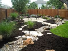 Water feature disappearing into a dry creek bed with a large flagstone patio set in decomposed granite with native grasses and boulders.
