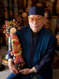 Artist with his kokeshi doll. Kokeshi are Japanese dolls, originally from northern Japan. They are handmade from wood, have a simple trunk and an enlarged head with a few thin, painted lines to define the face. The body has a floral design painted in red, black, and sometimes yellow, and covered with a layer of wax. One characteristic of kokeshi dolls is their lack of arms or legs. The bottom is marked with the signature of the artist
