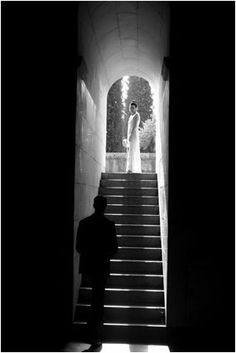 This is a wedding photo of the groom looking up the stairs to the bride.