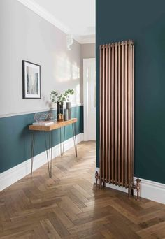 This dark green and light grey hallway with wood flooring is light and welcoming: 'A horizontal band of colour at ground level which includes painting the same colour on the skirting board will look great and help to reduce the appearance of scuffs and wear,' says Marianne Shillingford. (Photo: Galvanised antique copper vertical radiator, The Radiator Company).