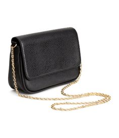 Black. Small shoulder bag in grained imitation leather. Flap with magnetic catch, gold-colored metal chain shoulder strap, and one inner compartment with