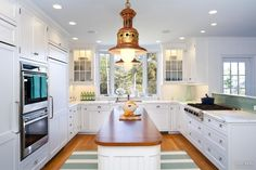 Large copper and brass lamps enhance the nautical feel of this new kitchen in a holiday home near the ocean.