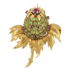 Gold, Platinum, Peridot and Ruby 'Thistle' Clip-Brooch, Tiffany & Co., Schlumberger   Centering a cluster of round peridots, accented by 7 small round rubies, capped by a gold leaf plaque centering one round cabochon ruby within platinum petals, supported by detailed curved gold leaves and stem, signed Tiffany, Schlumberger