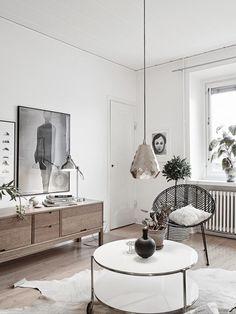 meuble tv en bois de design scandinave épuré dans le salon aménagé avec une table basse ronde et blanche, un tapis en peau de vache et une suspension en laiton facettée