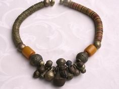 by Anne Marie of BeadArt Austria | Necklace; A lovely collection of all together about 26 antique bronze bells from the Yoruba Tribe in Nigeria , in various shapes and sizes are the focal point of this necklace. Large bronze beads and African amber (ophenolic resin) are on each side. The rest of the necklace is bakelite heishi from the African Trade period. The two sides are different just to show the two choices, you can have if you were to purchase the piece. | {No Longer Available}
