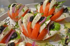 Freshly made and Featured on the Mozzarella Station: Stuffed Tomatoes with Fresh Homemade Mozzarella, garnished with Olives, Red Onion & Basil, YUM! — at Joe Leone's Italian Specialties.