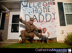 welcome home sign made out of a sheet... kids handprints for stars and stripes! homecoming