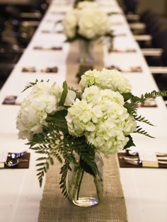 Hydrangeas in Mason jars on a burlap runner.
