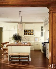 The cozy kitchen of a Lake Forest, Illinois, cottage offer seating around the spacious island