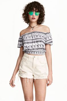 Top curto ombros descobertos: H&M LOVES COACHELLA. Top curto de ombros descobertos em jersey macio com brilho. Tem elástico no decote, mangas borboleta curtas e franzido em ponto smock no cós.