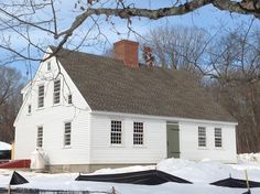 Cape Cod with a center chimney and batten board door.