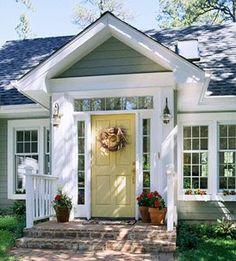 gray house with green undertone, brick and golden yellow door