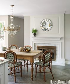In the breakfast area of a New Jersey kitchen designed by Caitlin Wilson, a farmhouse table is surrounded by French bistro chairs from Decor N More.   - HouseBeautiful.com