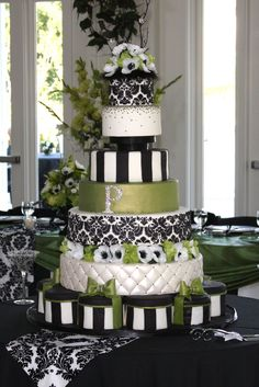 Green  Black and White Damask Wedding Cake - 7 Tiered cake with damask pattern on two tiers. Embellished with Swarovski rhinestone mongram and a few on the pillowed tier. Bows are accented also with Rhinestones and avocado luster dust. Black and White stripes make a good base for this masterpiece and bring attention up to the middle elevated tier.