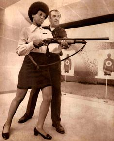 """Saundra Brown, 28, the first black woman on the Oakland police force gets instructions on how to shoot a shotgun by police rangemaster Adolph Bischofberger. Saundra graduates Friday near the top of her class after 15 weeks of criminal law, report writing, first aid, firearms training and defensive tactics. 'I really feel very confident now,' she said, 'but before I was totally afraid. I didn't want to be around a gun.'"""" Dec 17 1970"""
