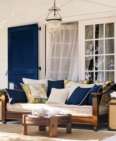 Coast Living...Beach house outdoor living on the back porch. Gorgeous Wood framed sofa, great throw pillows very chic in navy