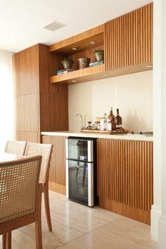 Varanda gourmet com canto para bar. Projeto de reforma e design de interiores em apartamento de 180 m2 em Moema, São Paulo. Decoração contemporânea com materiais acolhedores criam ambiente sofisticado e acolhedor.