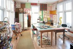 I'd had a sewing room just like this. Love the windows and all of the sun light coming in!
