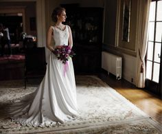Hycroft Manor in Vancouver - Bride with flowers looking out window - Natural Light and formal bridal portraits by Vancouver Wedding Photographer Caroline Ross