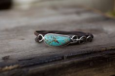 "Nevada Turquoise along with hand pulled wire in combination with a triple wrap of distressed brown leather.  1""x.50"" Turquoise*One of a kind, please advise desired size at checkout."