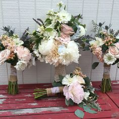 Bride and bridesmaids bouquets for a chic, rustic country wedding wrapped in burlap and lace. Soft muted colors using, blush, cream and lavender flowers. #flowersbytravispayne #bridalbouquet #bridesmaidsbouquet, #burlapandlace #thistle #peonies #roses #scabiosa #silverdollareucalyptus #astilbe #veronica #dahlia #weddingflowers #blush #lavender #bouquets #countrywedding #countrybouquets #soft #muted.