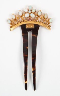 A opal hair comb, set with three oval opals either side of an opal flower motif of five oval opals and one circular, with seed pearls. Circa 1900.