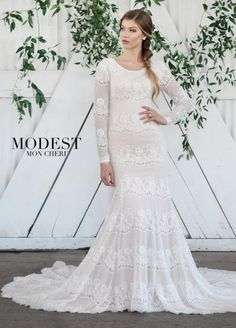 Style TR21861 is Boho chic at its very best. This exquisite soft allover lace fit and flare modest wedding gown has cap sleeves under illusion lace long sleeves with eyelash cuffs, a softly scooped neckline, a dropped waist, and covered buttons that cascade down the back onto the chapel train and to the scalloped eyelash hem. Lovely for any type of wedding.