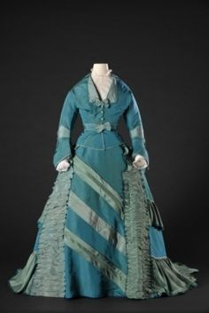 Dress in turquoise and light blue silk taffeta, 1865-69. This dress in turquoise and pale blue taffeta silk has a train and a separate waistband with panels at the back, with large decorative buttons. The daytime corsage has a V-shaped neckline and pagoda sleeves. It was worn over a chemisette. The dress is decorated with ribbons, bows, flouncing and bands of densely gathered fabric. Source: MODEMUSEUM HASSELT