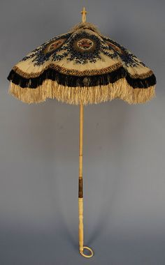 Ivory silk canopy parasol with blue floral and gold metallic brocade, oval reserves filled with bouquets of red and pink flowers, blue silk fringe with woven band over longer ivory silk fringe, Chinese export carved ivory handle with ring and finial, wooden shaft with brass slide, 1850's