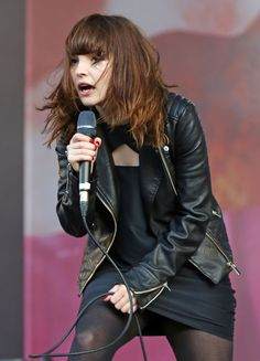 Celebrities In Leather: Lauren Mayberry performs on stage in a black leath...