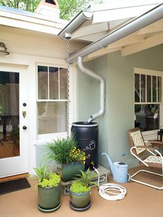 Eco-Friendly Outdoor Patio:  Gutters on this Longwood, Florida, home direct runoff into a rain barrel. A hose connected to the rain barrel makes it easy to hand-water a few pots nearby. A rain chain also guides water from the roof into a large pot. (Photo: Ralph Anderson)