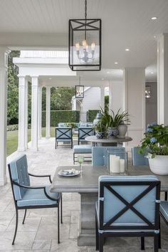 White pillars line this gorgeous covered patio features wrought iron, square-back, dining chairs dressed in blue cushions surrounding a gray outdoor dining table lit by a beautiful Osborne lantern hung from a white beadboard ceiling boasting recessed lighting.