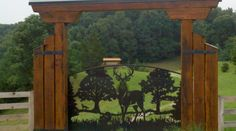 Image of an arched driveway gate with deer pine trees turkey and fox.