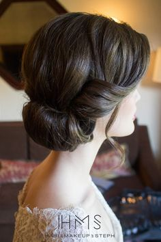 Bridal up-do: soft curl on the side and a rolled bun at the nape of the neck