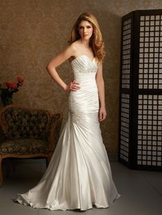 Style: 2464    A fabulous fitted gown in a charmeuse satin. The sweetheart neckline is ruched while a gorgeous Swarovski crystal band accents the empire waistline.