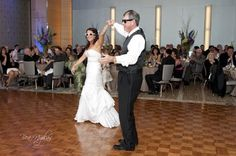 Hundreds of guests watch as a father spins his newly married daughter on the dance floor at her wedding reception. Both are wearing sunglasses, just one of the many fun details of this wedding, held at the luxurious Fairmont Hotel in downtown Pittsburgh. As she spins around her dad, the bride's strapless taffeta mermaid dress swirls around her ankles. The John Parker Band provided the soundtrack for this moment and many others throughout the evening. http://www.jpband.com/weddings.html