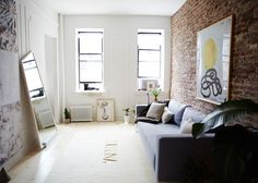 "AfterThe living room is now a whitewashed respite from the hustle and bustle of the city. ""Since [moving to] New York five years ago, I am more into a minimal, modern aesthetic,"" says Taymour. ""I think the transition from L.A. to NYC really showed in my last place — I was still a little hippie at heart."" Painting (above sofa): Suzannah Wainhouse."