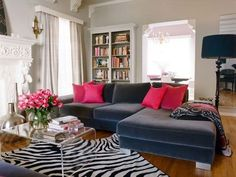 light grey walls. deep grey sofa. pops of magenta and black and white