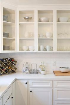 Fabulous white kitchen features upper cabinets, with no doors, used as display shelves filled with white pottery.