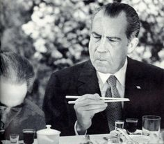 President Richard Nixon trying to figure out how to use chopsticks while visiting in China. 1972.