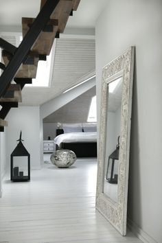 All white bedroom with some fab accessories. I'm loving the large mirror leaning against the wall too!