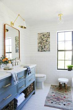 amenagement salle de bain, meuble massif en bleu canard, tapis rectangulaire en style ethnique sous le meuble wc, miroir au cadre en bronze, luminaire applique au-dessus du miroir en couleur or avec abat-jour classique, fenêtre rectangulaire au cadre en noir