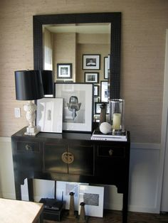 Ron Marvin    black and beige chinoiserie foyer design with sand beige grasscloth wallpaper, chair rail Asian black console table, alabaster lamp with black lamp shade, glass hurricane, gallery frames books and black mirror.