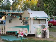 Love this old vintage camper!  Notice the flowers and picket fence!  Great and inspiring old camper with a nice little RV/camper garden touch too!
