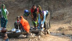 Women filling their water jars from a well posed for a photo.
