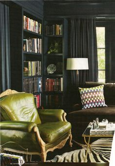 Magnificent Green Leather Chair on a black canvas. Sofa pillow picks up the green of the chair and colors of the books.