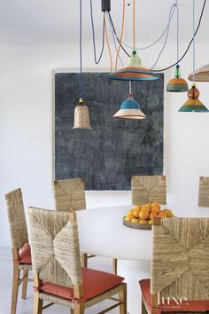 The gray sobriety of Sam Messenger's painting in the family room's dining area balances folksy PET Lamp pendants made from recycled bottles covered in colorful weaves. Noir's Neva chairs, with Perennials' Ishi fabric for the cushions, add a hint of Scandinavian modern design.