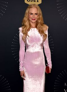 Nicole Kidman  in NASHVILLE, TN October 18th, 2017 In occasion of the 2017 CMT Artists Of The Year Awards, Nicole Kidman chose to wear Versace. The actress was stunning in a look from the Versace Spring Summer 2018 runway. She wore a long sleeved, pale pink velvet dress with architectural shoulder detail and knotted accent at the bust. She accessorized her look perfectly with mirrored Versace clutch.