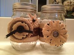 Burlap wrapped mason jars with flowers.